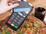 Using payment terminal with contactless credit card, cashless paying for vegetarian pizza in restaurant, finance and banking concept